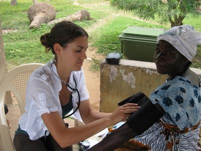 Volunteer nurse checking the blood pressure of a woman in Ghana