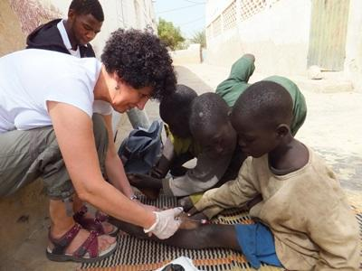 A nurse volunteering in Senegal treats a street child during an outreach.
