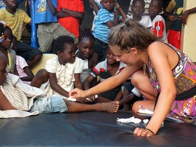 A Projects Abroad intern helps dress wounds at a care centre for children in Togo.