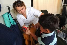 A Nursing volunteer in Bolivia assists a young boy during her internship.