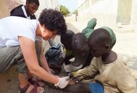 An volunteer on the Nursing Internship in Senegal looks at a child's wounds.