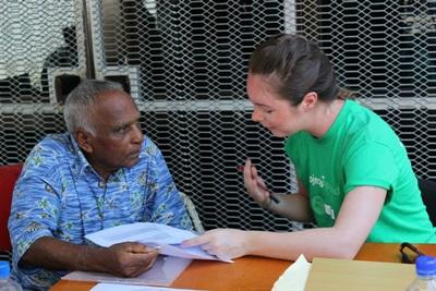 A Projects Abroad talks to a local man about the importance of healthy eating during an outreach in Fiji.