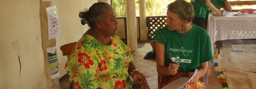 A Projects Abroad intern discusses the importance of healthy eating with a local woman at a Nutrition Project abroad.