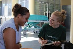 Nutrition volunteer in Samoa chats with a woman about healthy eating during her internship.