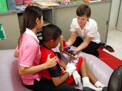 A Projects Abroad intern in Cambodia helps a local caregiver provide treatment for a child at a care centre.
