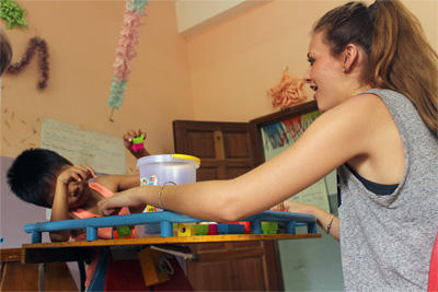An Occupational Therapy intern helps a child with therapy exercises at a special needs centre in Cambodia.