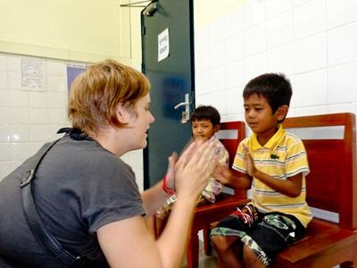 An Occupational Thereapy intern plays a hand clapping game with children at a school in Cambodia.