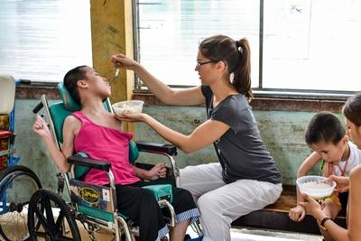 Projects Abroad intern at the Occupational Therapy Project in Vietnam helps a child with disabilities eat lunch.
