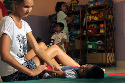 A Projects Abroad Physiotherapy intern treats a Cambodian child with special needs at the National Borei for Infants and Children in Cambodia