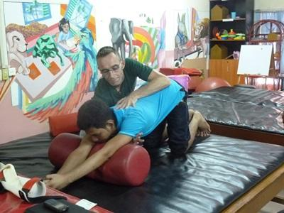 A physiotherapist voolunteering in Cambodia does exercises with a child at a special needs centre in Cambodia.