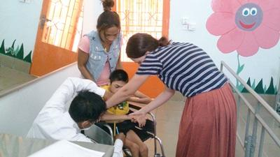 Physiotherapy intern treating a Cambodian child