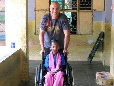 A physiotherapy intern takes a young patient for a walk outside a clinic in India