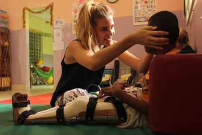 A Physiotherapy intern spends time with a child at a rehabilitation centre in Cambodia.