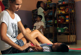 A Physiotherapy intern in Cambodia assists a child during her volunteer project.