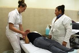 A volunteer on the Physiotherapy Internship in Mexico learns new stretches from her supervisor.