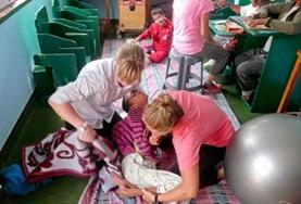 Physiotherapy interns help a young child during treatment in Nepal.