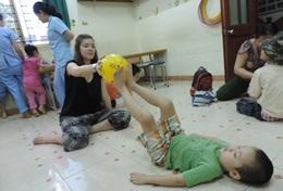 A Physiotherapy intern in Vietnam plays a game with a boy during a session.