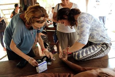 A Cambodian man receives treatment from Projects Abroad Public Health interns during an outreach.