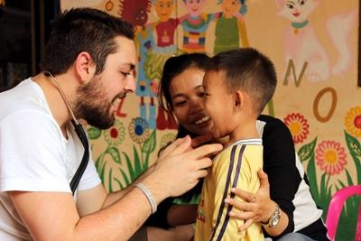 A child at  akindergarten in Cambodia has his teeth and throat checked by a Projects Abroad Public Health intern.