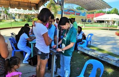 A Projects Abroad intern on the Public Health Project checks weight during an outreach in the Philippines.