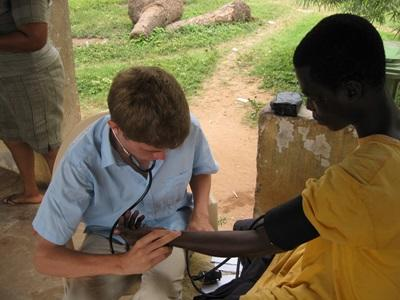 A Projects Abroad Public Health intern checks heart rates during an outreach in Ghana.