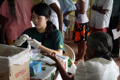 A Projects Abroad Public Health intern checks blood sugar levels during an outreach in Sri Lanka.