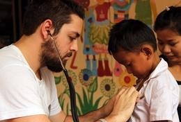 A public health intern examines a young boy in Cambodia during his volunteer project.