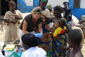 A public health intern in Ghana works with a group of young children and women during a medical outreach on her volunteer project.