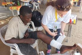 A Public Health intern in Togo does a medical checkup on a local child during her volunteer project.