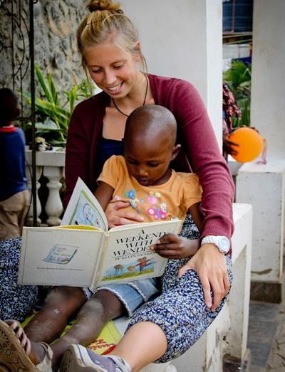 A child with speech difficulties in Tanzania pratices reading aloud with a Projects Abroad intern.