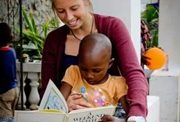 A volunteer on the Tanzania Speech Therapy Internship reads a story to a young child.