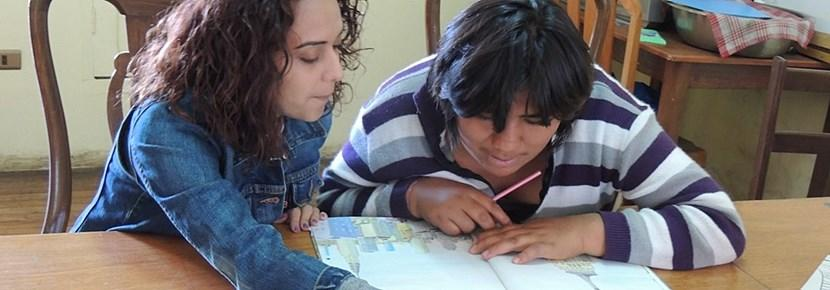 A Projects Abroad intern studying speech therapy works with a child at a special needs school abroad.