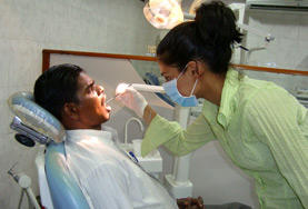 A volunteer on a Dental Internship abroad examines a man's teeth in a developing country.