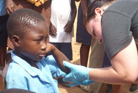A nursing volunteer abroad checks a young boy's wound during her internship in Kenya.