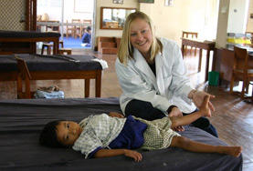 A Physiotherapy School Elective student assists a young child with his therapy.