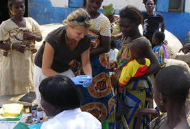 A public health volunteer abroad assists during an outreach.