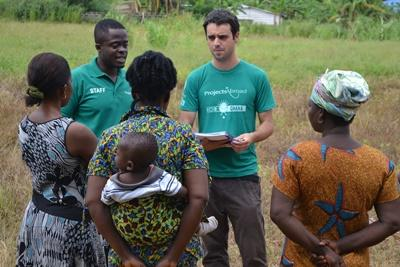 Two Microfinance interns discuss business opportunities with local women in Ghana.