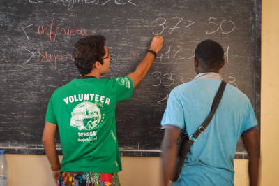A former talibe learns basic math from a Projects Abroad Microfinance intern in Senegal.