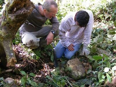 A professional archaeologist volunteering abroad with Projects Abroad examine s a local site.