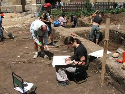 Archaeologists volunteering with Projects Abroad in Romania examine their findings at an excavation site.