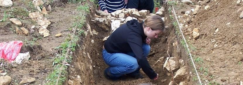 An archaeologist volunteerig abroad examines an excavation site.
