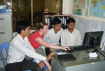 Local businessmen discuss how to approach and solve a problem with a business consultant volunteering in Cambodia.