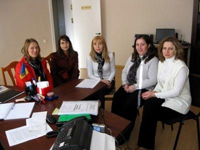 Professional consultants volunteering in Romania attend a meeting at an office.