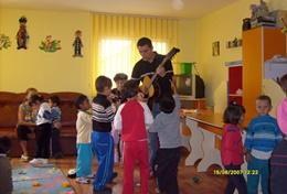 A professional volunteer art therapist uses music for an activity with young children in Romania.