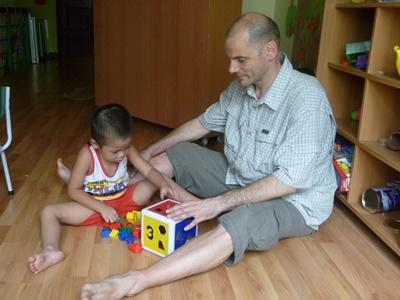 A professional volunteer in Vientam spends time with a child at a care centre.