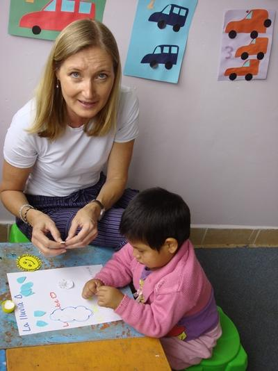 A social worker volunteering in Bolivia interacts one-on-one with a child at a care centre.