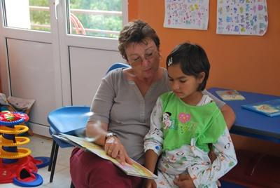 A professional social worker volunteering in Romania reads with a child at a care centre.