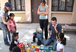 Professional social workers explain a game to children in Bolivia.