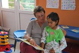 A professional social worker volunteering in Romania works with a young child in the classroom.