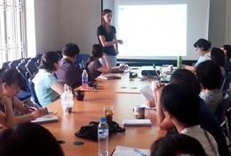 A professional volunteer social worker gives a presentation to local staff at a Vietnam placement.